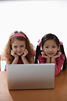 two young girls playing with laptop - Asia Images Group