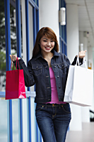 Young woman smiling and holding up shopping bags - Asia Images Group