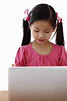 Young Chinese girl looking at laptop - Asia Images Group