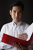 head shot of man holding folder - Asia Images Group