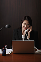Woman sitting at her desk talking on phone - Asia Images Group