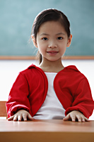 Portrait of young girl sitting at desk in classroom - Asia Images Group