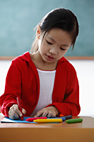 Young girl coloring with crayons - Asia Images Group