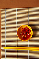 Small bowl of red chillies and chopsticks. - Asia Images Group