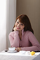 Young woman sitting in cafe near window - Asia Images Group