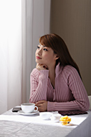 Young woman sitting at table looking our window - Asia Images Group