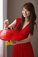 Young Chines woman wearing red dress holding red lantern - Asia Images Group