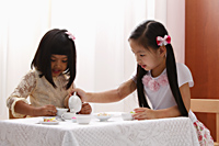 two little girls having a tea party - Asia Images Group