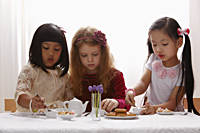 Three young girls having a tea party - Asia Images Group