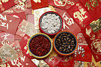 Different red envelopes scattered on table with melon seeds in bowls. - Asia Images Group