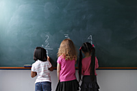 rear view of 3 young girls writing on chalk board - Asia Images Group