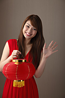 Young woman wearing red dress, holding red lantern and waving - Asia Images Group