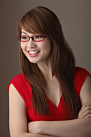 Young woman in red dress wearing red sunglasses looking away and smiling - Asia Images Group