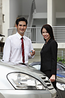 Man and woman standing in car park - Asia Images Group