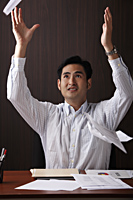 man sitting at desk throwing paper in the air - Asia Images Group