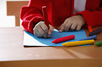 cropped shot of young girl coloring with crayons - Asia Images Group