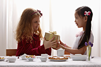 two girls sharing a gift - Asia Images Group