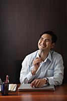 Man sitting at desk smiling - Asia Images Group