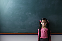 Young girl with pony tails standing in front of chalkboard - Asia Images Group