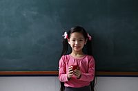 Young girl holding a red apple in front of chalk board - Asia Images Group
