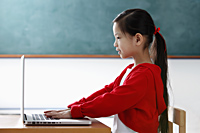 Profile of young girl looking at the computer - Asia Images Group