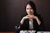Woman sitting at desk with hands folded - Asia Images Group