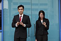 Man and woman wearing suits holding phones - Asia Images Group