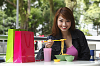 Young woman sitting outside eating noodles - Asia Images Group