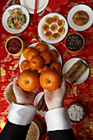 Hands holding oranges over table with Chinese food - Asia Images Group