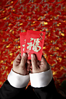 Cropped shot of hands holding red envelopes - Asia Images Group