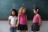 three young girls standing in front of a chalk board, smiling at each other - Asia Images Group