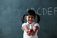 young girl holding out apple in front of chalkboard - Asia Images Group