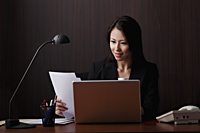 Chinese woman sitting at desk looking at papers - Asia Images Group