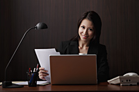 Chinese woman sitting at desk smiling - Asia Images Group