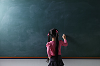 rear view of young girl writing on chalkboard - Asia Images Group