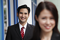 man smiling with woman in out of focus in foreground - Asia Images Group