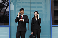 Man and woman wearing suits and talking on phones - Asia Images Group
