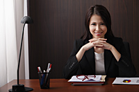 woman sitting at desk with folded hands smiling - Asia Images Group
