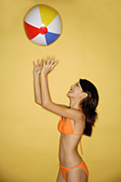 Young woman in bikini, throwing ball in air - Asia Images Group