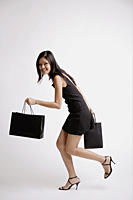 Young woman carrying shopping bags - Asia Images Group