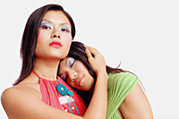 Two women, one looking at camera, the other resting with eyes closed - Asia Images Group