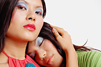 Woman looking at camera, another woman leaning on her shoulder, eyes closed - Asia Images Group