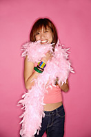 Young woman looking at camera, wearing feather boa - Asia Images Group