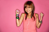 Young woman smiling, listening to mp3 player - Asia Images Group