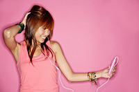 Young woman holding mp3 player, looking away, hand behind head - Asia Images Group
