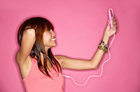 Young woman holding mp3 player, looking up, hand behind head - Asia Images Group