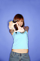 Young woman against blue background, making hand sign - Asia Images Group