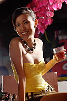 Young woman holding drink, looking at camera - Asia Images Group