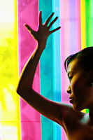 Woman leaning hand against coloured glass - Asia Images Group