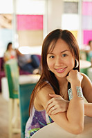 Woman leaning on table, smiling, looking at camera - Asia Images Group